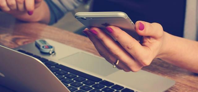 Ein handy in der Hand und vor dem laptop sitzen. Alle Projekte im Überblick.
