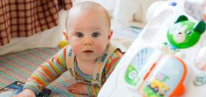 Ein Baby schaut fasziniert auf den Fotografen. Es liegt auf dem Boden und schaut auf..