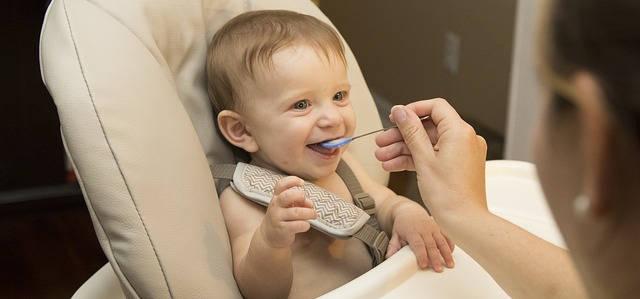 Das Kind sitzt im Hochstuhl und schaut eine Person an. Dabei öffnet es den Mund, um den Löffel entgegen zu nehmen, der ihm an den Mund gehalten wird.