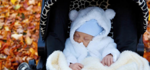 Ein Baby ligt in weißen Klamotten eingepackt im Kinderwagen. Es schläft.