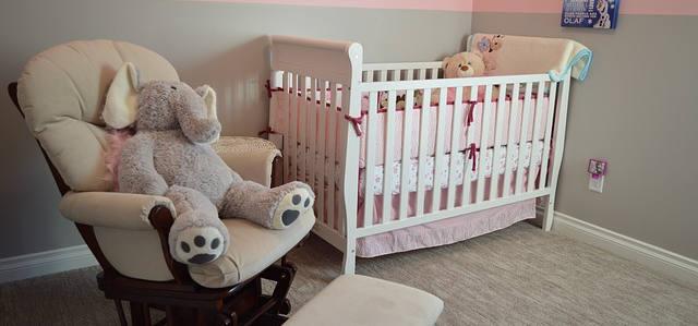 Ein Sessel und ein babybett in einem Raum. Auf dem Sessel sitzt ein Teddy. Das Babybett sind weiblich aus., wegen den Farben rosa und weiß.