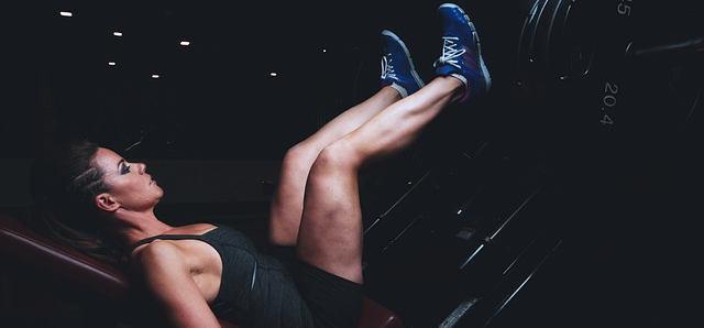 Eine junge Frau die an der Beinpresse die Beine trainiert. Sie hat blaue Schuhe an.