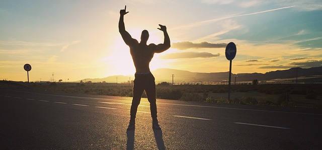 Ein Bodybuilder im Sonnenuntergang. Man sieht nur seine Konturen, da die Sonne alles weitere verdeckt.