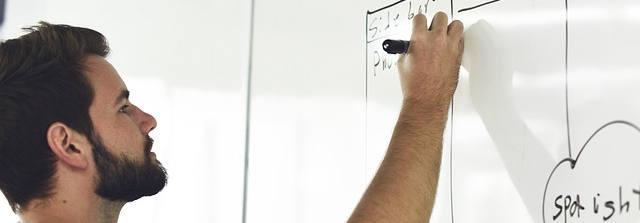 Ein junger Mann mit Bart schreibt gerade etwas an eine Tafel.
