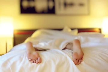 Füße schauen aus einem Bett heraus. Wenn sie gehören weiß man nicht. Vermutlich schläft die Person. Sie liegt auf dem Bauch, da die Füße nach unten zeigen.