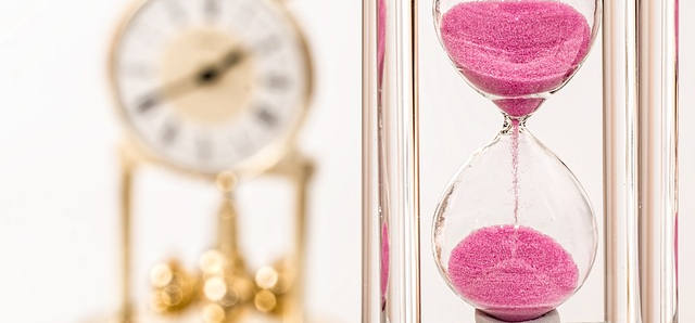Zwei verschiedene Uhren sind zu sehen. Eine Sanduhr im Vordergrund und eine moderne im Hintergrung. Der Sand der vorderen ist pink.