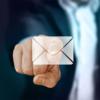Ein Zeigefinger eine Mannes drückt auf das Symbol eines Briefes. Der Mann trägt einen Anzug. Er ist nur verschwommen im Hintergrund zu erkennen.