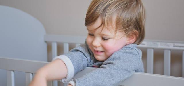 Das süße Kind ist blond und greift über das Gitter des Kinderbetts. Es hat ein lächeln auf dem Gesicht.