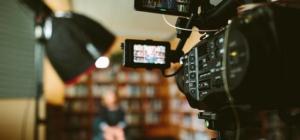 Der Hintergrund verschwommen und im Vordergrund eine Filmkamera mit der aufgenommen wird