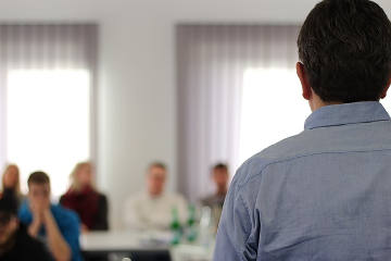 Ein Mann hält einen Vortrag vor sitzenden Personen. keine Person ist erkenntlich.