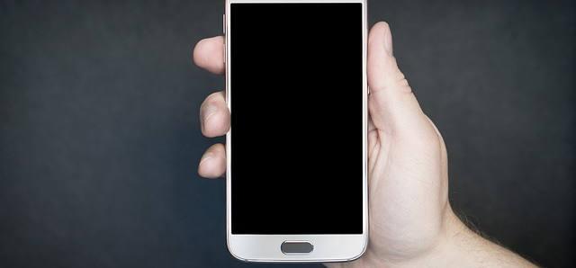 Eine Männerhand hält ein Smartphone in der Hand. Es ist ausgeschaltet. Der Bildschirm ist schwarz..