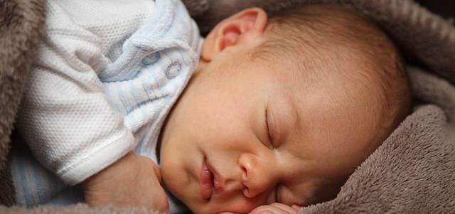 Ein Baby am schlafen. Sehr süß in eine Decke eingewickelt.