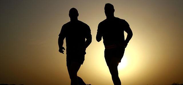 Die Sonne geht unter und zwei Männer Joggen nebeneinander .