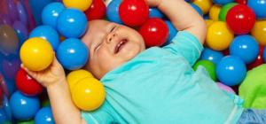 Ein kleines Kind liegt im Meer voller Bälle und freut sich.