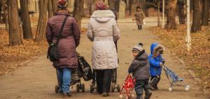 Zei Frauen schieben Kinderwagen vor sich her. Man sieht sich von hinten eine Allee entlang laufen. Neben ihnen sind zwei Kinder die auch zwei Kinderwagen schieben.