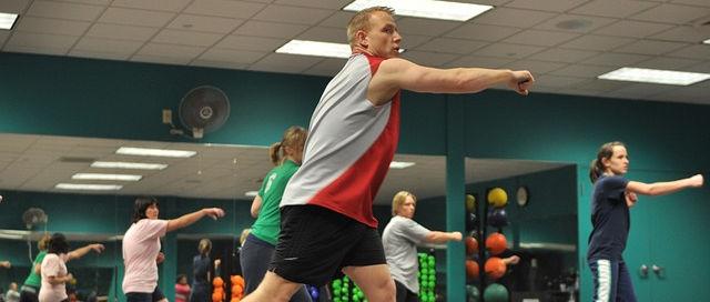 Ein Trainer steht vorne, mittig und macht eine Bewegung vor. Diese wird von den weiblichen Kursteilnehmerinnen in Hintergrund nachgemacht.
