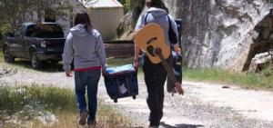 Zwei Meschen Tragen gemeinsam eine Kühlbox. Außerdem hat die linke Person eine Gitarre um sich geschnallt.