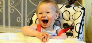 Ein Kind isitzt in seinem Hochstuhl und amüsiert sich. Es ist komplett verschmiert.
