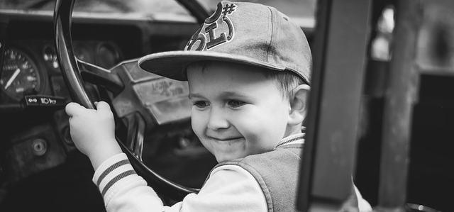 Ein jung, der eine Kappe auf hat, sitzt hinter einem Steuer. Dieses Steuer ist viel zu groß. Das Kind ist aber glücklich.