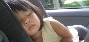 Ein asiatisches Kind schläft in einem Kindersitz.