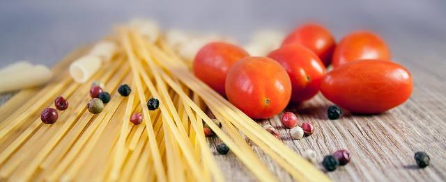 Spaghetti liegen auf einem Hölzernen untergrund. Sie sind ausgepackt . Daneben liegen kleine Tomaten. Verstreut sind Pfefferkörner zu finden.