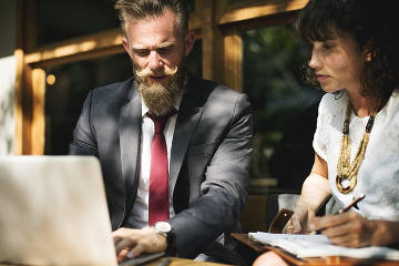 Ein Mann im Anzug mit Laptop und eine Frau in modernen Klamotten.