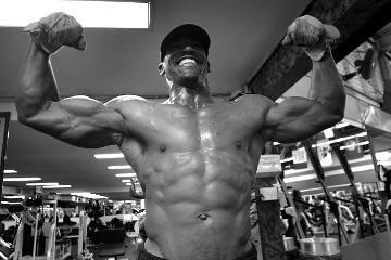 Ein schwarz weiß Bild. Ein Mann spannt seine Muskeln an und präsentiert sie im Fitnessstudio. Dabei hat er die Arme gehoben um seinen recht beeindruckenden Bizeps zu zeigen.