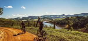 Zwei Radfahrer fahren durch eine Landschaft. Grüne Hügel und ein Fluss sind zu sehen. Der Weg auf dem die Radfahrer fahren ist sandig und steinig.