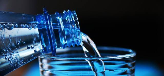 Wasser wird gerade aus einer Flasche in ein Glas geschüttet.