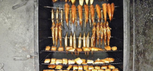Verschiedene Fischen und Stücke liegen oder hängen im Räucherofen.
