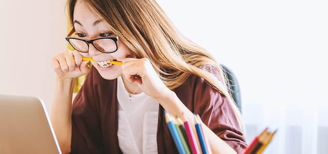 Eine asiatische Frau schaut auf ihren Laptop und beißt auf einen Stift.