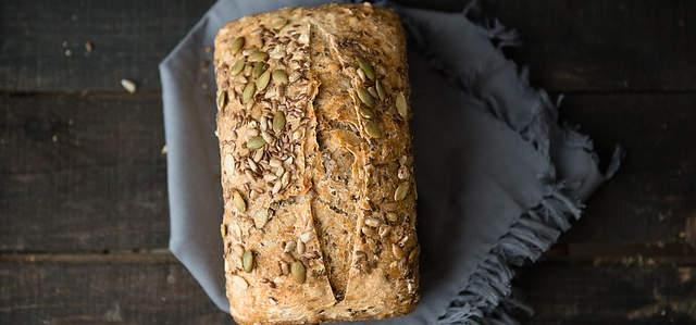 Ein schönes, helles Brot liegt auf einem hölzernen Tisch, dazwischen ein braunes Tuch. Das Brot hat oben drauf Körner.