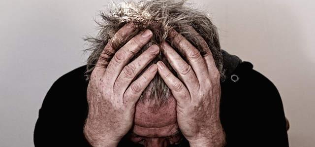 Ein Mann schlägt die Hande über den Kopf. Er scheint älter zu sein, was seine Haut verrät.