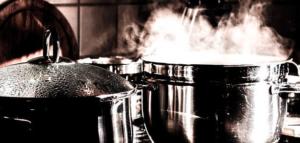 Zwei Kochtöpfe. Aus dem einem steigt dampf aus. Das Bild ist in schwarz weiß und einem leichten rot gehalten.