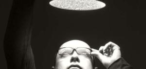 Ein Mann mit Brille und einer Glatze schaut in eine über ihm stehende Lampe.