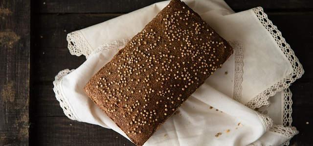 Ein dunkleres Brot mit kleinen Körnungen auf dem Brot. Darunter ein weißes Tuch auf einem Holzboden.