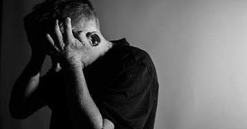 Ein Mann schlägt die Hand an die Schlefe. Sein Gesicht ist nicht zu erkennen. Das Bild ist schwarz und weiß gehalten.