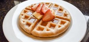 Eine Waffel auf einem Teller. Beide haben eine runde Form. Auf der Waffel ist Sirup und eine Erdbeere.